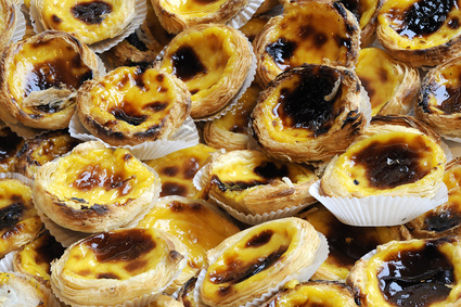 Portuguese Custard Tarts (Pastel de Nata or de Belém).   A close-up of traditional Portuguese custard pastries that consists of custard in a crème brûlée-like consistency caramelized fashion in a puff pastry case.